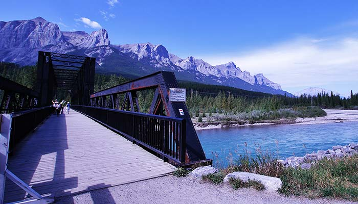 An image of a walking bridge crossing the Bow River in Canmore